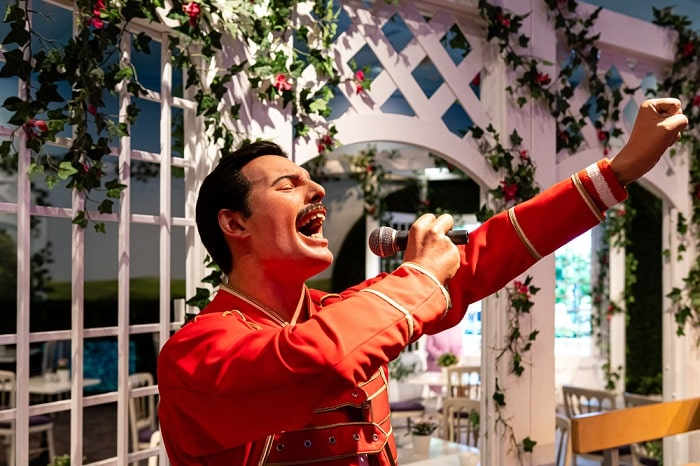 A waxwork statue of Freddie Mercury wearing a red jacket and holding a microphone in London.