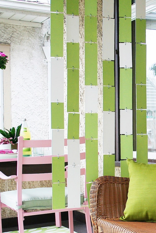 A DIY dorm room divider made of panel boards painted green and white and linked together by cable chains to hang like a curtain from the ceiling.