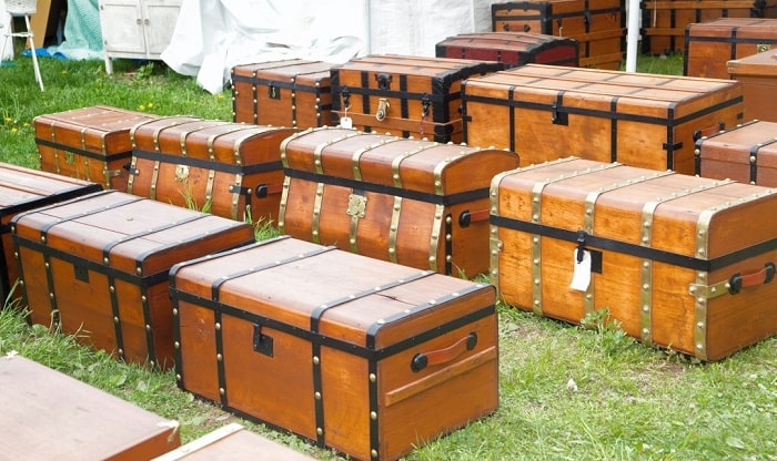 Various types and sizes of wooden storage trunks on a grass lawn.