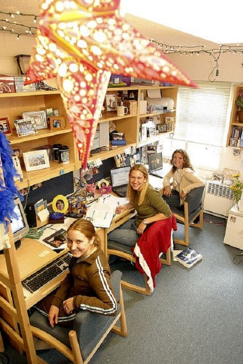 A three-person dorm room with fairy lights hanging on the ceiling and book shelves adorned with picture frames of various designs and other knickknacks.