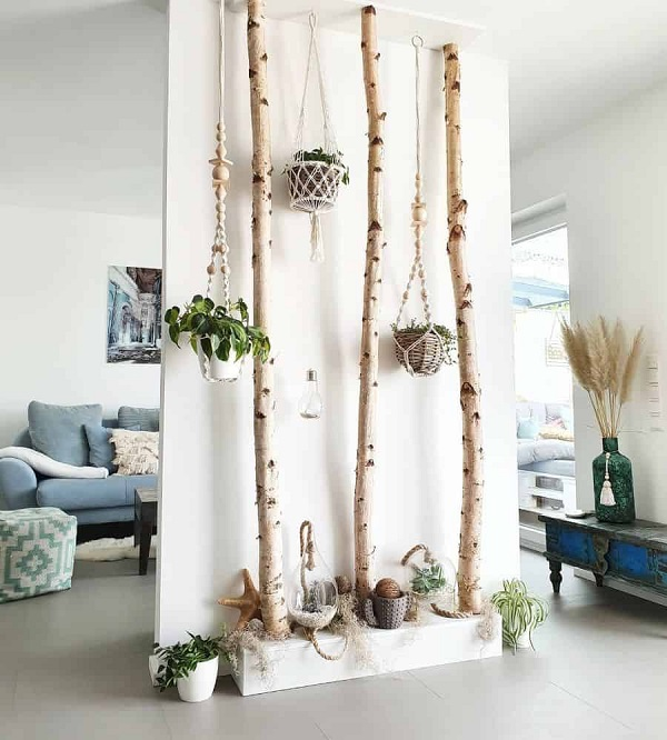 An outside-on-the-inside dorm room divider made of a tall white cardboard divider, dried forest branches, and various succulents.