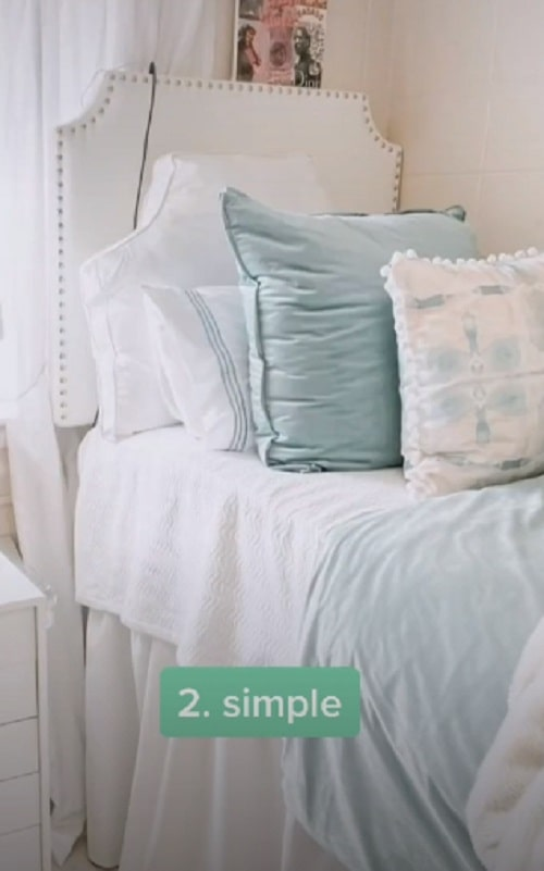 A dorm room with pastel blue beddings and a white tufted button upholstered faux leather headboard.