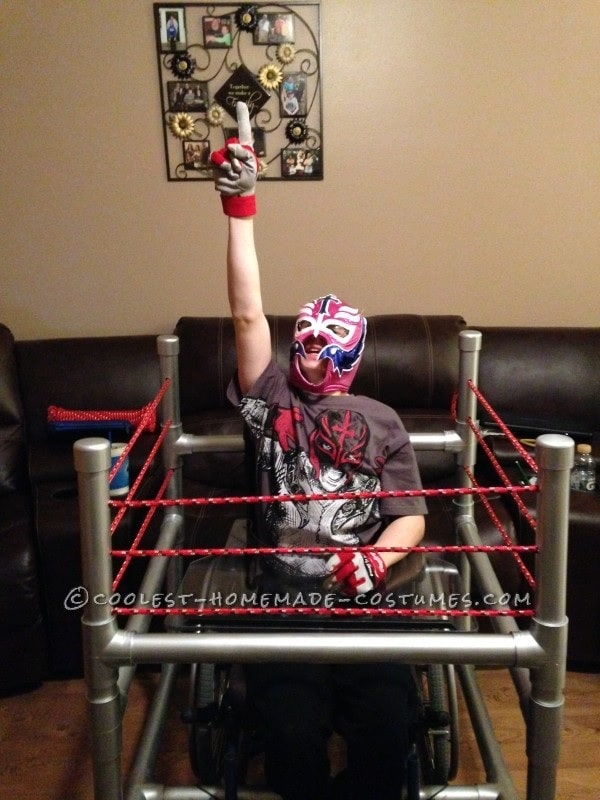 A guy in a professional wrestler costumer, wearing a wrestling mask and gloves with an improvised wrestling ring made of red cotton rope and spray-painted ring posts attached to his wheelchair.