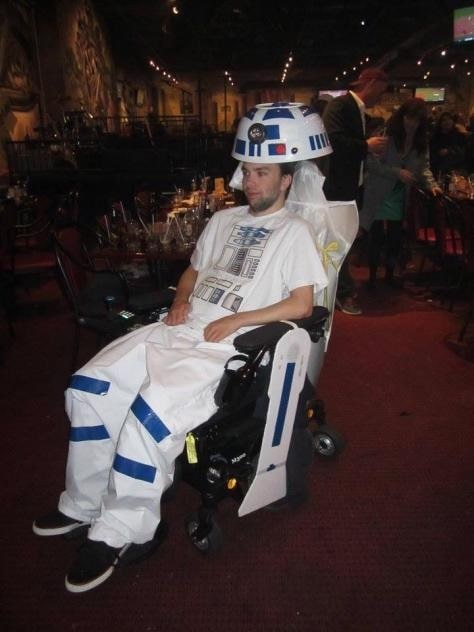 A guy in an R2-D2 costume, wearing a white printed shirt and pants with blue duct tape, and an improvised headgear.