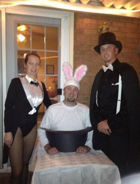 A man in a rabbit out of a hat costume, wearing a white shirt, bunny ears, and an improvised magician's hat attached to his torso, with a woman dressed as a magician's assistant and a man dressed as a magician on either side of him.