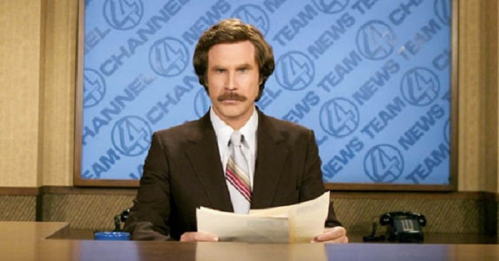 Will Ferrell as Ron Burgundy, wearing his anchorman suit-and-tie outfit, brown wig, and mustache.