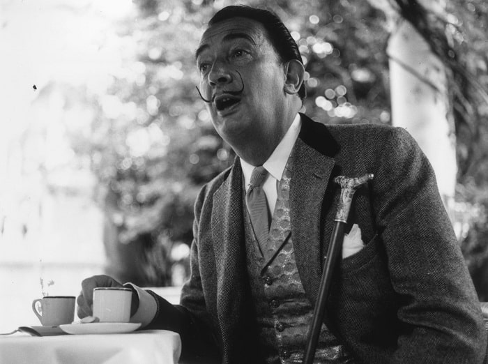 A black and white photo of Salvador Dali with his signature pointy mustache, wearing his three-piece suit and holding his silver-tipped walking cane.