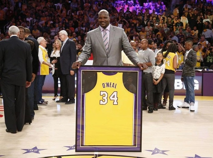 Shaquille O'Neal wearing a suit while holding a framed jersey with his name and number.