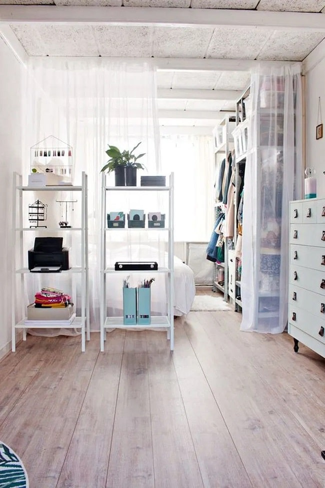 A DIY dorm room divider made of sheer white curtains and matching freestanding bookshelves that contain various items.