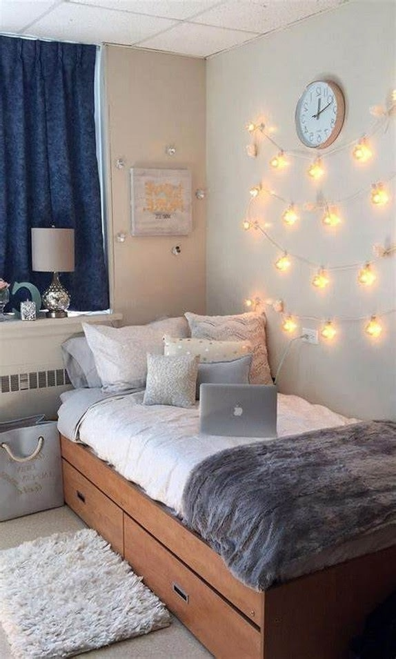 A dorm room adorned with simple fairy lights hung under a round wall clock.