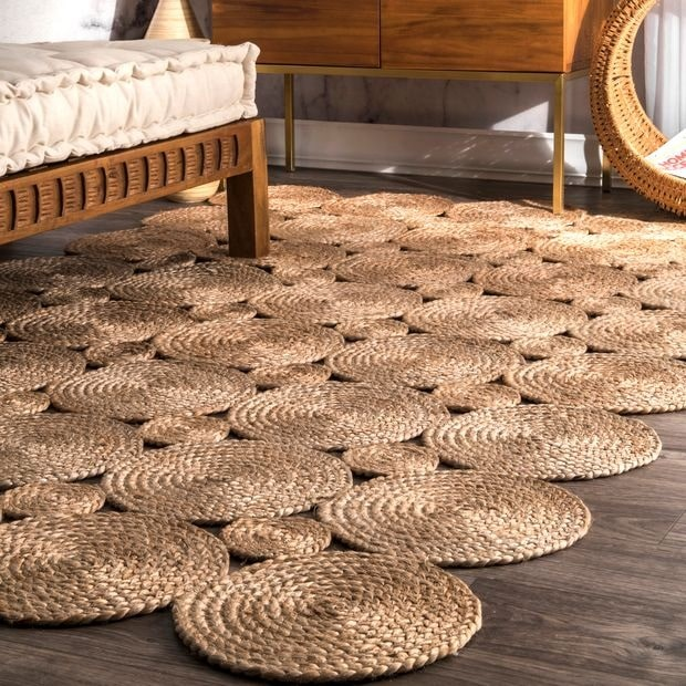 A room with a large woven jute area rug and matching woven furniture to complement the wooden accents.