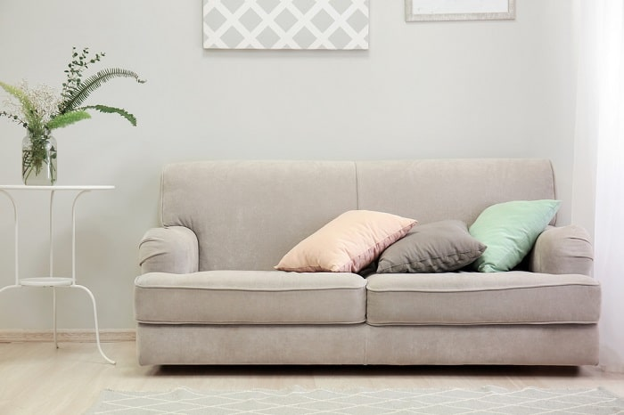A simple gray couch with pink, gray, and teal throw pillows on top and an indoor plant beside it.