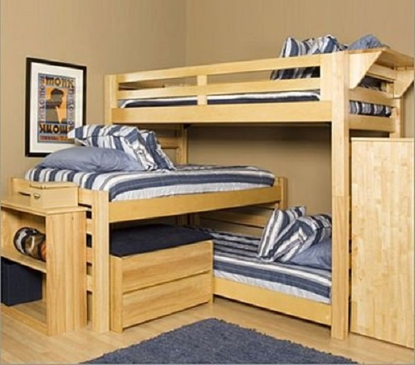 A three-person dorm room with space-saving corner beds in blue and white striped beddings plus a blue shaggy area rug to complement the motif.