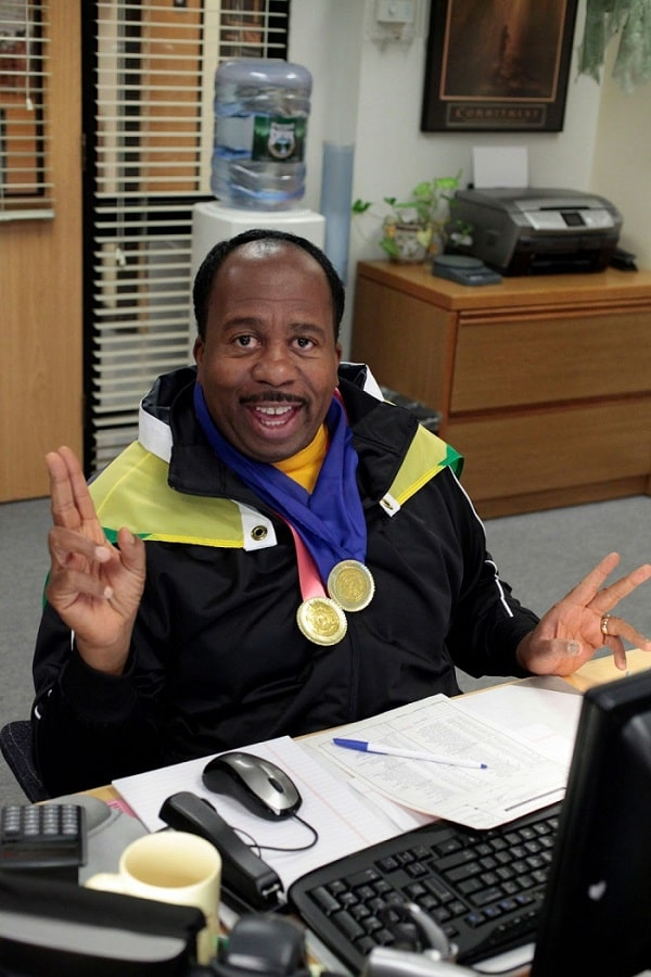 Stanley Hudson in a Usain Bolt costume, wearing a black tracksuit, medals, and a Jamaican flag draped around his shoulders.