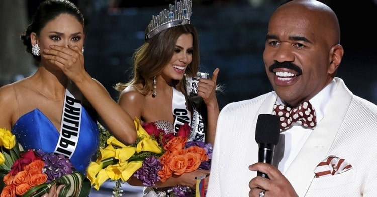 Steve Harvey with his signature mustache, wearing his white suit with red and white polka dot bowtie during a Miss Universe pageant with Miss Colombia Ariadna Gutiérrez and Miss Philippines Pia Wurtzbach.