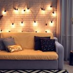 A room with warm white globe string lights hung on a white brick wall with a two-toned double bed and throw pillows.