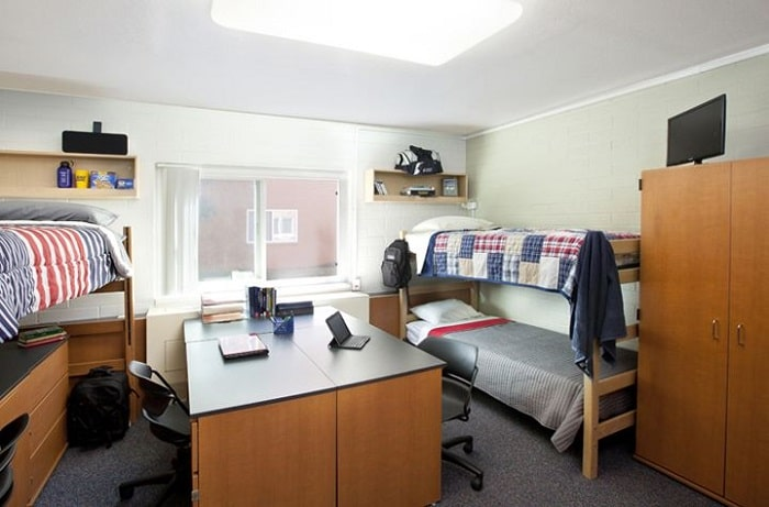 A three-person dorm room with a common study area in the middle that consists of study desks and swivel mesh computer chairs.