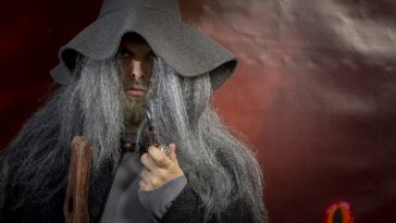 A man dressed as Gandalf the Grey from Lord of the Rings, with his long, hair, wizard's hat, and staff.