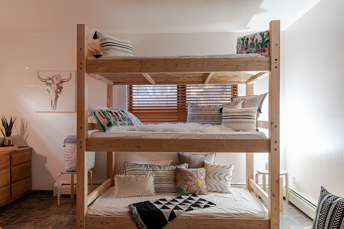 A three-person dorm room with a wooden bunk bed, neutral-colored beddings, and a geometric-print throw blanket.