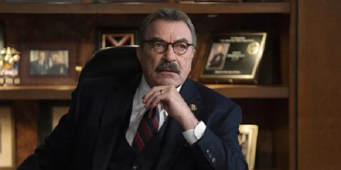 Tom Selleck in Blue Bloods with his signature mustache and wearing his slim-fit suit and tie with matching round-shaped spectacles.