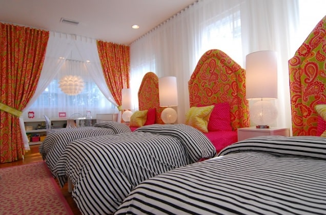 A three-person dorm room with black and white striped beddings, patterned headboards, and matching vibrant-colored curtains.