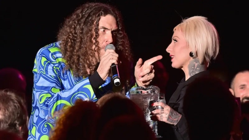 """""""Weird Al"""" Yankovic with his signature curly hair and mustache, wearing a psychedelic-print shirt and holding a microphone while talking to a woman from the audience."""