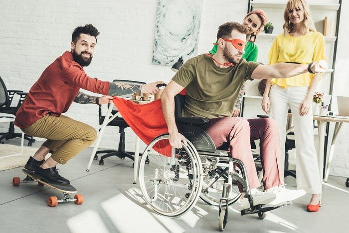 A man in a wheelchair wearing a superhero costume, having fun with his friends.