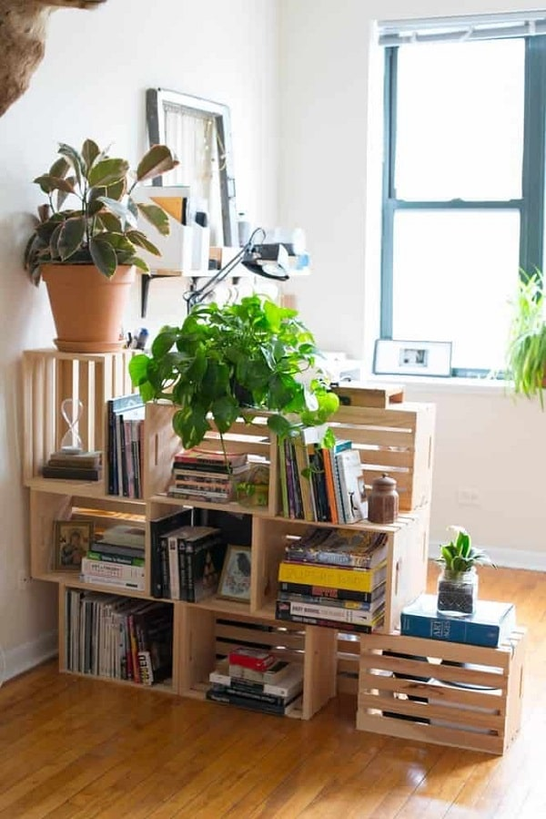A DIY dorm room divider made of wooden crates put together with some books placed inside them, along with some artificial plants.