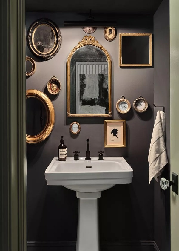 A bathroom with an antique-style mirror wall made of various shapes of mirrors with a vintage aesthetic.