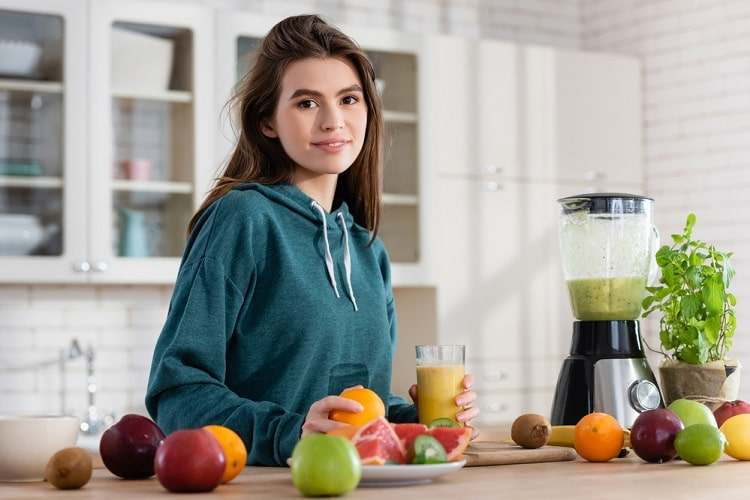 A college student in a teal hoodie holding a glass of smoothie with various fruits on the counter and a high-powered blender beside her.