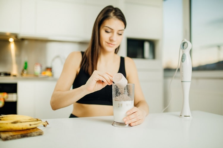A college student in workout clothes, making a banana protein shake using an immersion blender.