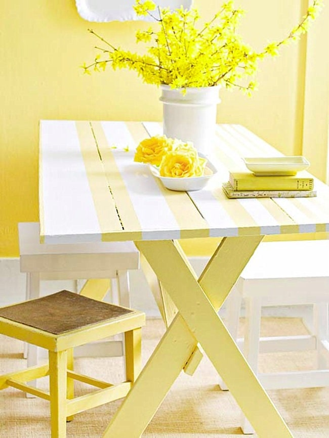 A bright indoor picnic table seating idea for a dorm room, with white and yellow tables and chairs, along with matching yellow artificial flowering plants.