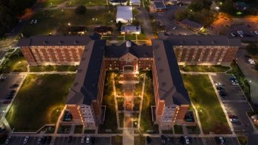 An aerial shot of a college dorm at night with lampposts that illuminate the walkways.