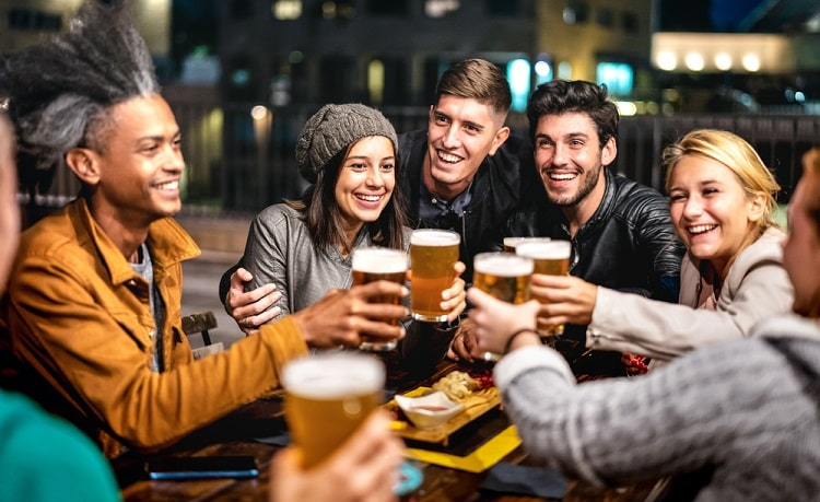 College dorm residents out with friends and drinking beer at night.