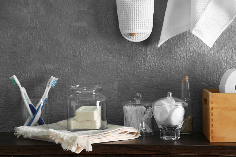 A corner of a gray-walled bathroom with glass containers for toiletries placed on top of a wooden surface.