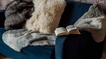 A teal-colored love seat with faux fur throw pillows and matching blanket, with an open book on the armrest.