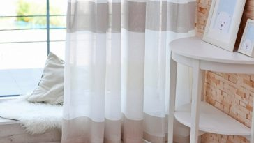 A dorm room with a sheer white and taupe curtain that doubles as a divider for privacy.