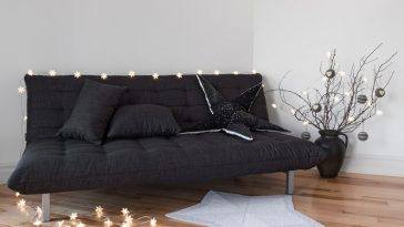 A dark gray futon with cozy lights in a dorm room space.