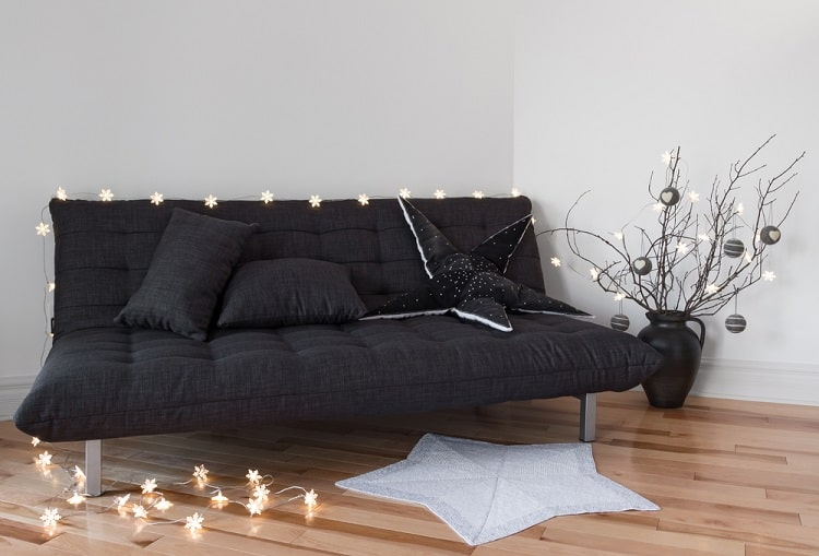 A dark gray mini futon with cozy lights in a dorm room space.