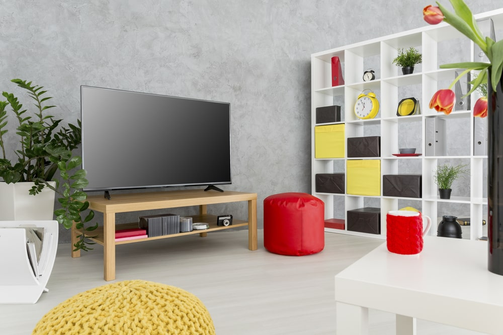 A minimalist light-colored wooden TV stand for a dorm room with red and yellow color accents.