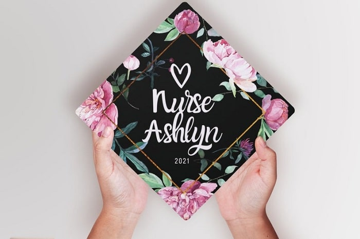 A nursing graduation cap with the graduate's name on it in white lettering surrounded by a gold bolder and floral edges.