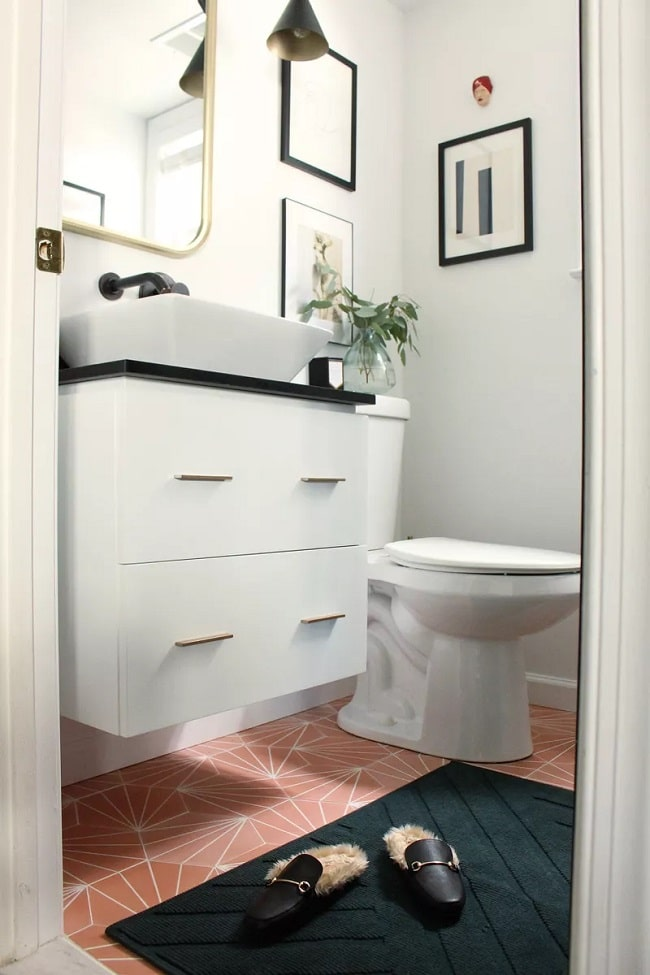 A bathroom with a fun bathroom floor made of light coral waterproof, self-adhesive contact-style wallpaper with white geometric prints.
