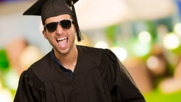 An overjoyed-looking guy in his graduation attire, wearing sunglasses and his graduation cap.
