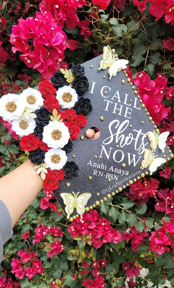 """An """"I call the shots now"""" nursing graduation cap adorned with various flowers and butterflies."""