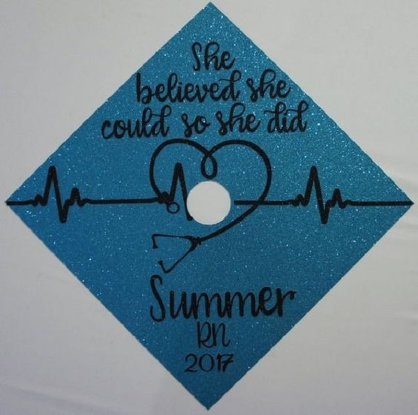 A nursing graduation cap with inspirational words and a stethoscope heart decal on a glittery blue base.