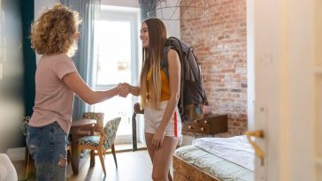 Two college students greeting each other as they move into their dorm room.