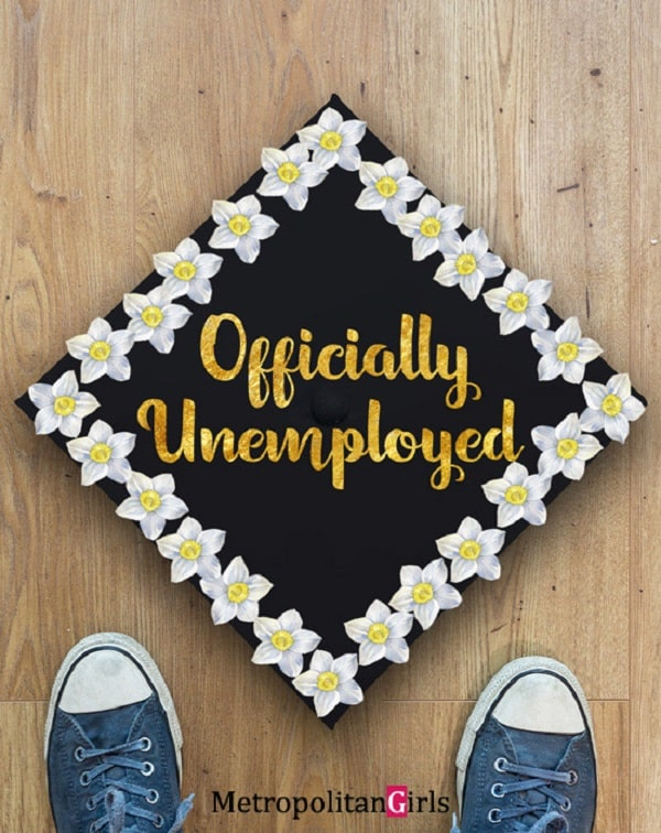 """A funny graduation cap adorned with gold """"Officially Unemployed"""" lettering and white flowers around the edges."""