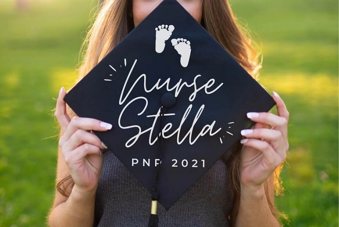 A pediatric nurse graduation cap with the graduate's name on it, along with baby footprint stickers.