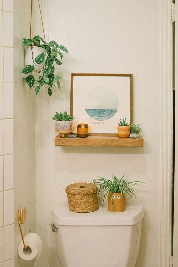 A bathroom decorated with artificial plants, one sitting on top of the toilet with googly eyes on the pot.