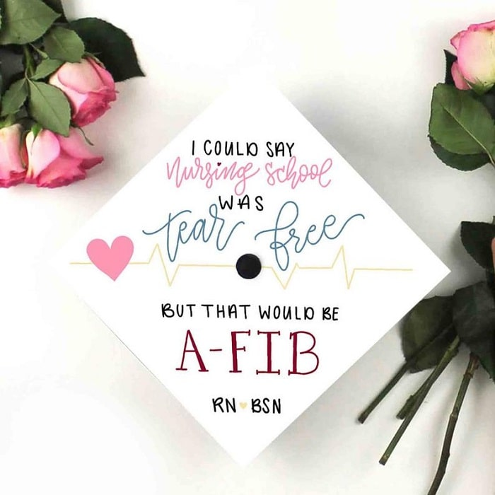A nursing graduation cap with a white base, a nursing pun, and a pink heart sticker to go with the lettering.
